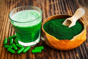 Spirulina smoothie, powder and pills on wooden background