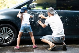 Father and daughter wash the car