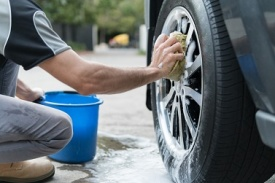 Man watching the wheel of a car with a sponge and soapy water