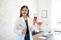Dietitian with weight scale and apple
